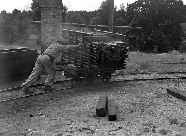 Thetford historic, man pushing logs