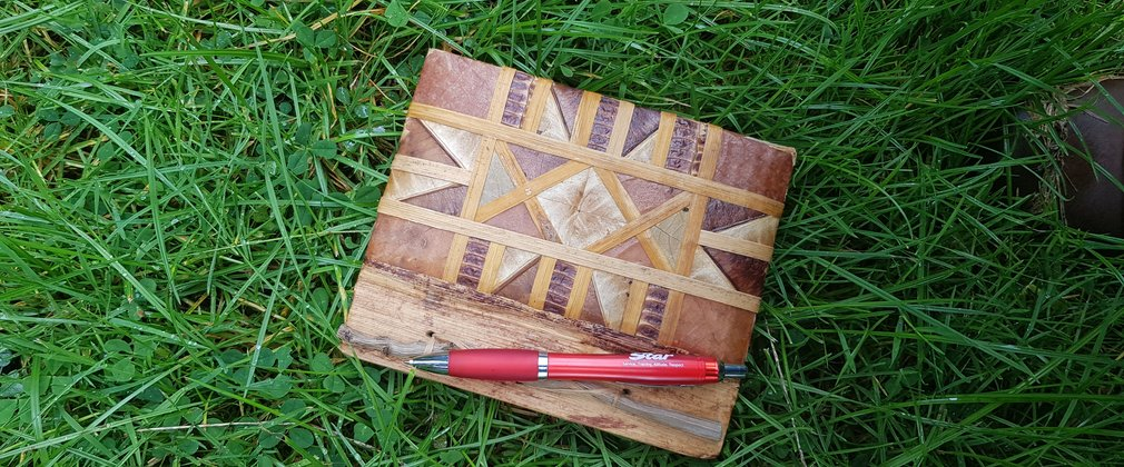 Notebook and pen on green grass