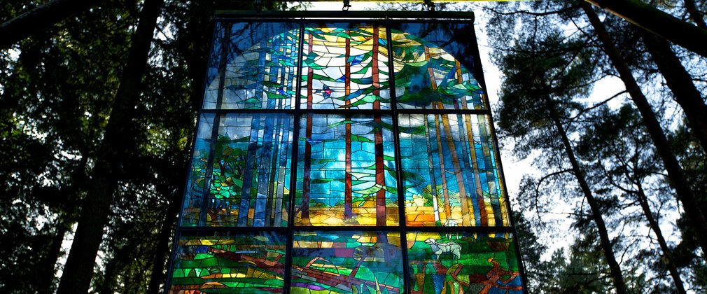 Stained glass pannel hanging in the canopy at beechenhurst sculpture trail