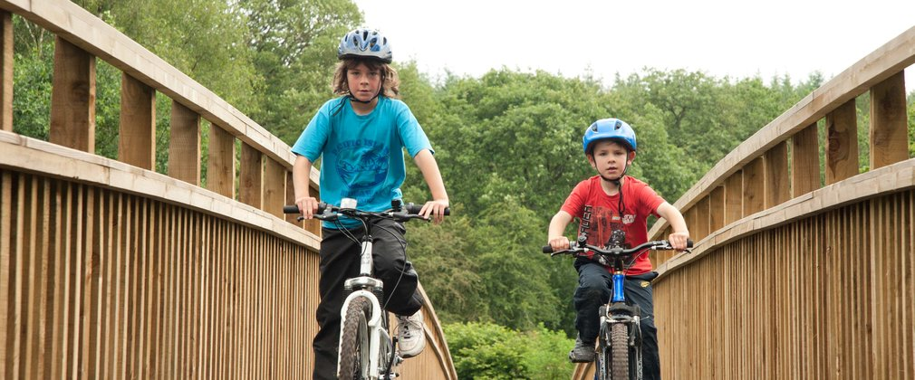 two boys cycling in the forest on a cycle route