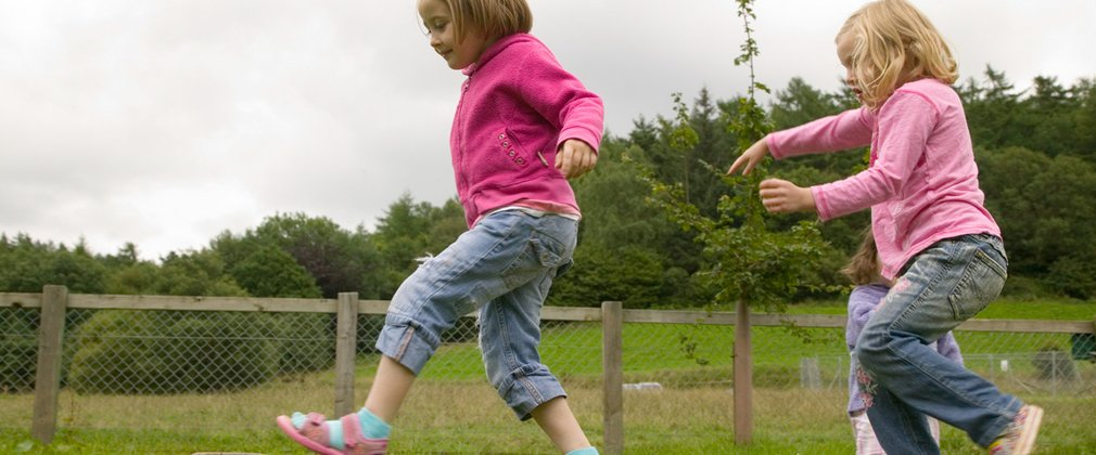 children balancing on wooden beam in play area in the woods
