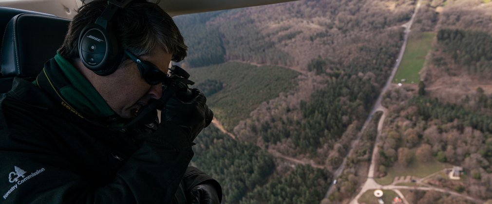 Man doing an aerial survey of the forest from a helicopter