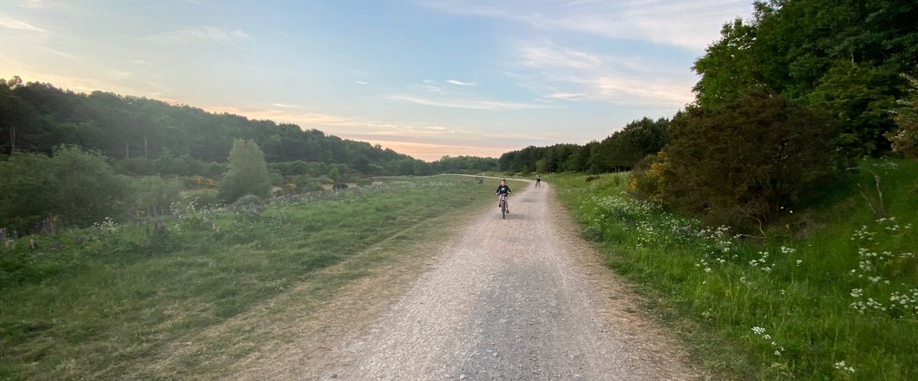 A girl biking in the distance at Boundary wood during sunset
