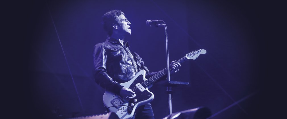 Noel Gallagher on stage holding his guitar.