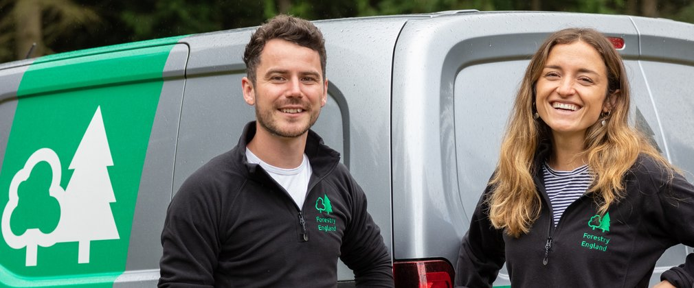 Group of Forestry England staff stood smiling in front of grey Forestry England van