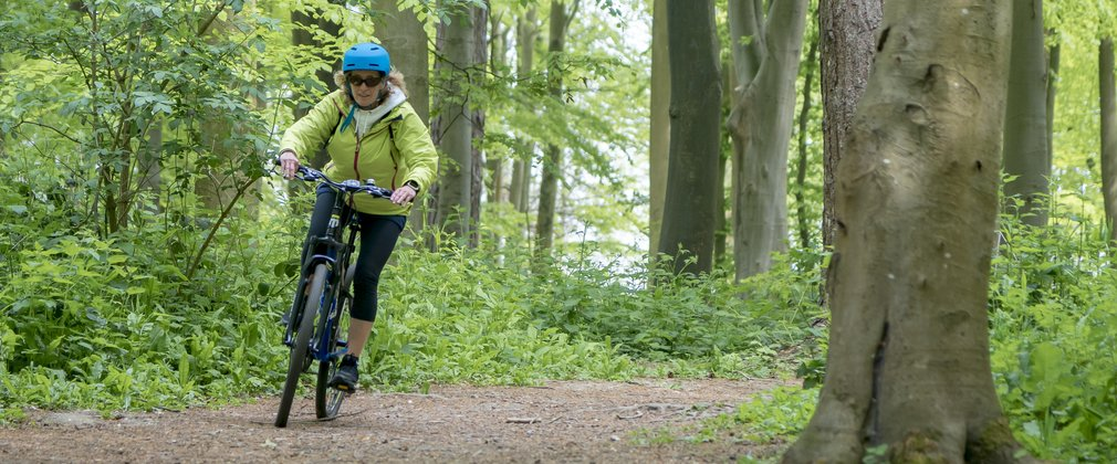 Woman on the easy cycle trail at Friston Forest
