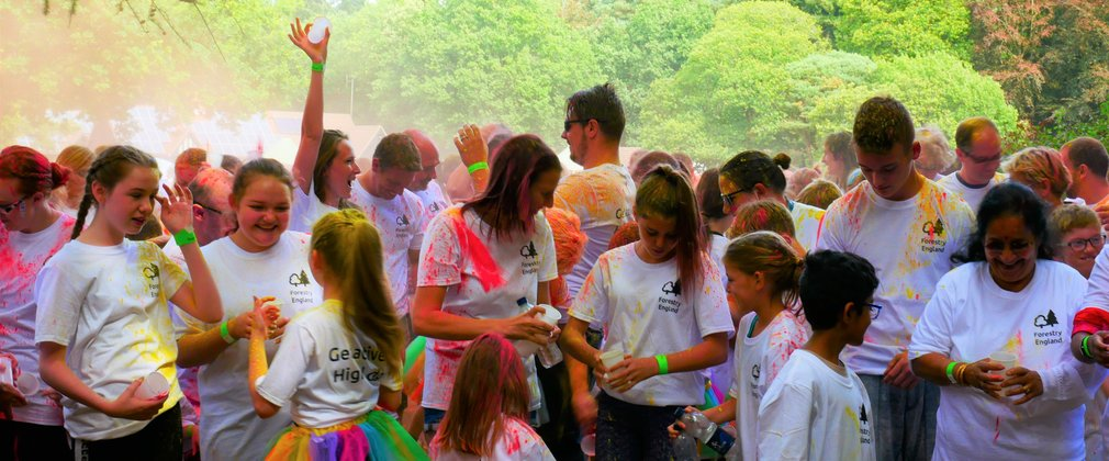 Group of people at colour run throwing powder paint