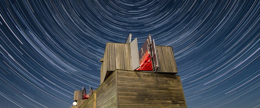 Kielder Observatory at night surrounded by stars