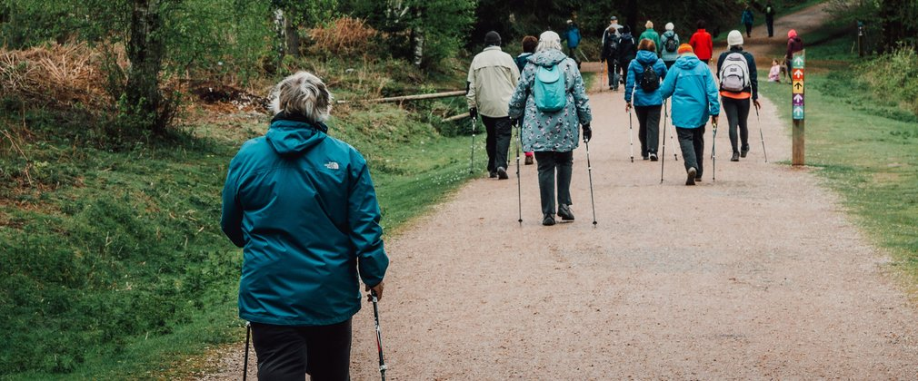 Over 50s nordic walking of gravel path in forest from behind