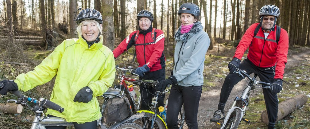Over 50s posing with bikes looking happy in the forest
