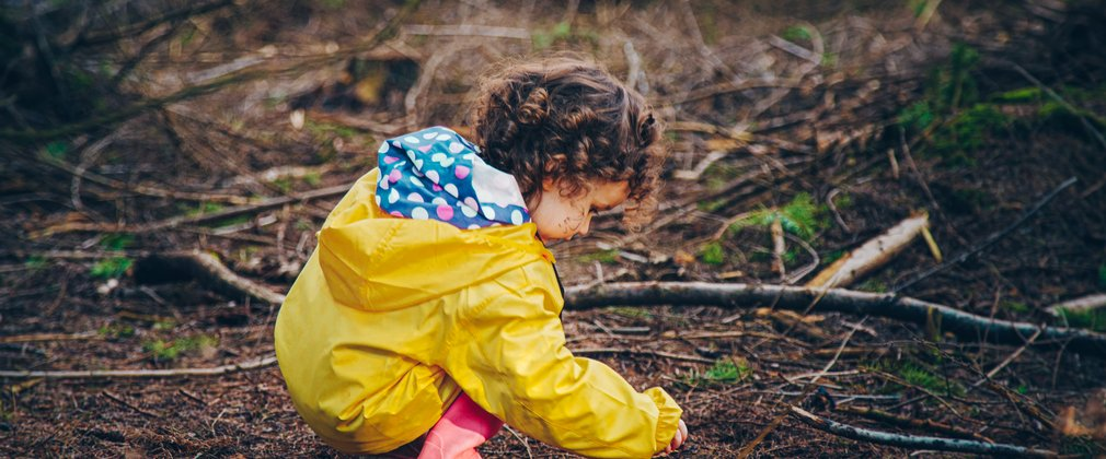 Young girl in yellow coat playing with pine needles on the forest floor
