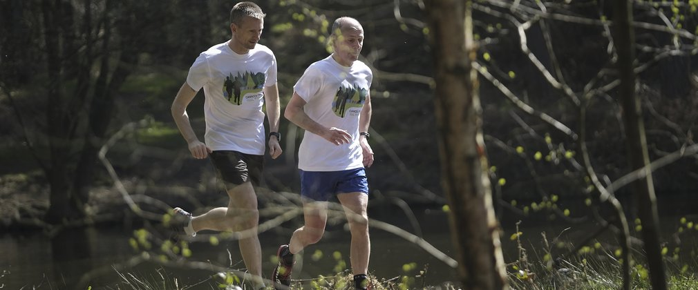 Two men running through the woods on a trail