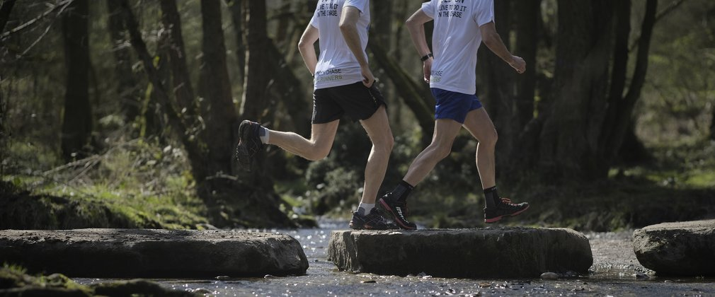 two runners crossing a stream on a running trail in the forest