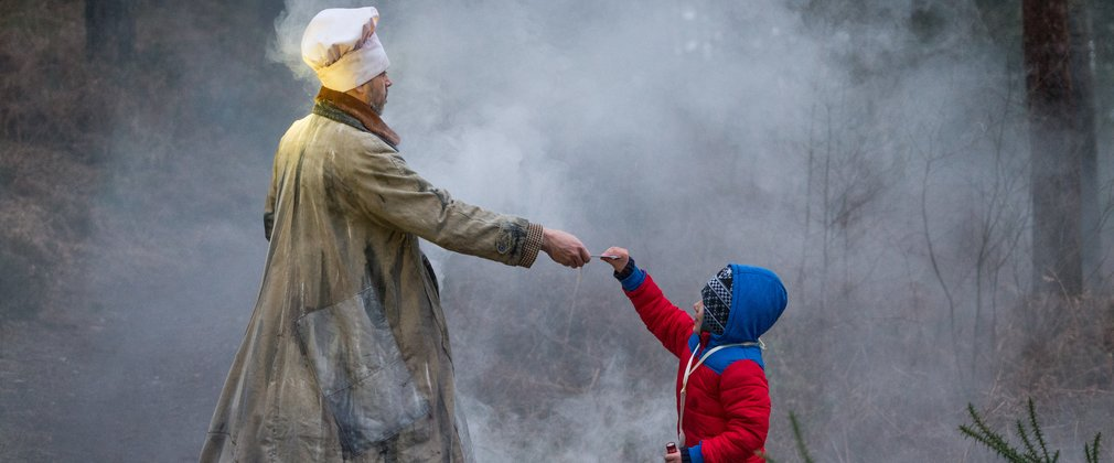 Theatrical figures reaching out a hand to a child