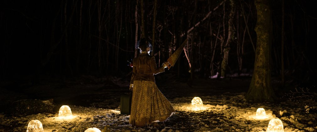Theatrical person in a ring of light in a forest