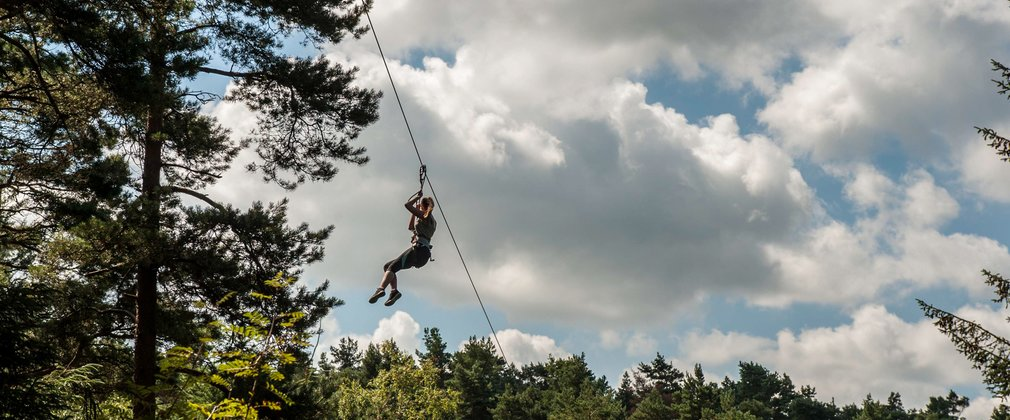 Person on a zip wire, high ropes course in the forest