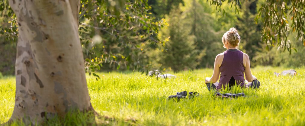 Woman sat on grass in sunshine in yoga pose