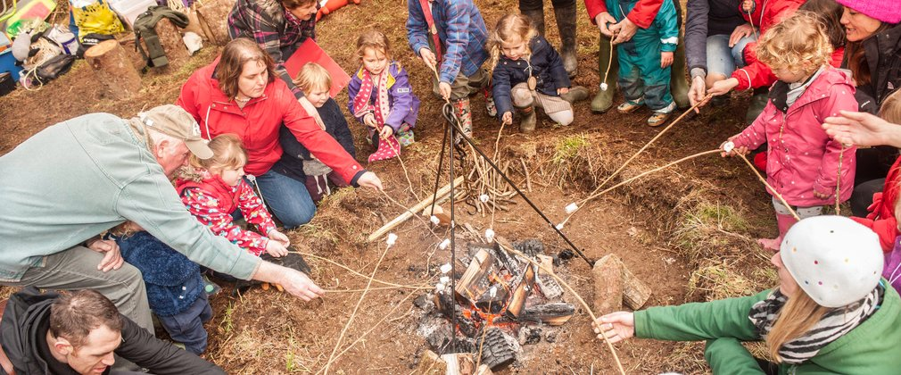 Large group of families sat around campfire toasting marshmallows