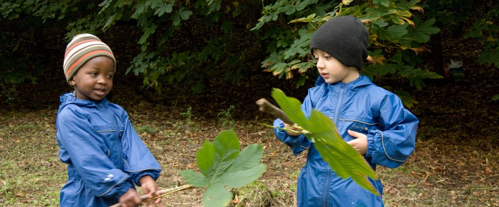 Two children playing with large leaves in the forest