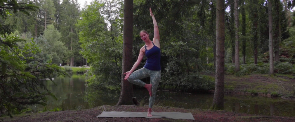 Woman teaching yoga in the forest