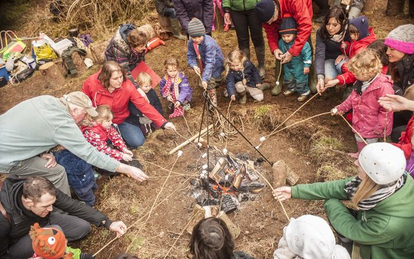 Children and parents are gathered round a campfire toasting marshmallows