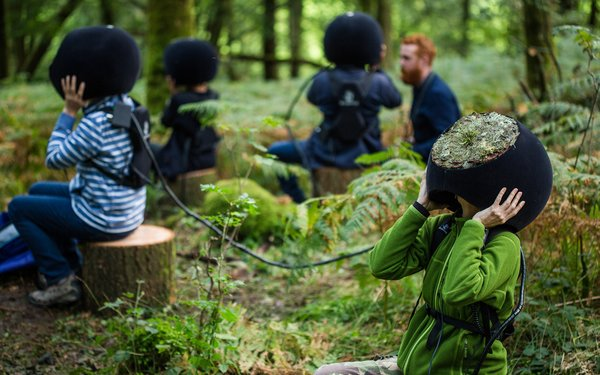 People sitting on logs in the forest with VR headsets