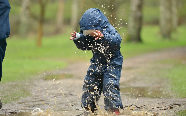 Child jumping in puddle and being splashed in the face