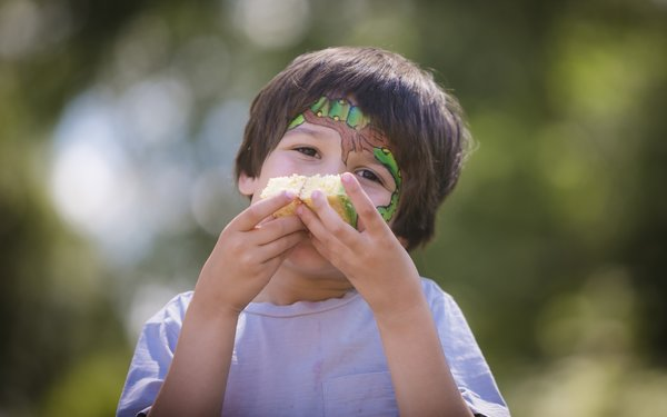 Boy with Gruffalo face paint eating a piece of cake