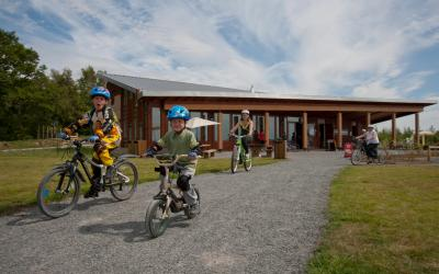 Family cycling away from the visitor centre