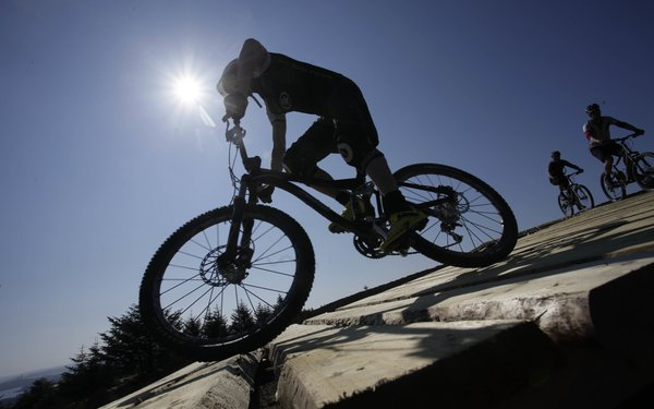 Mountain biker riding over timber flyover at Kielder