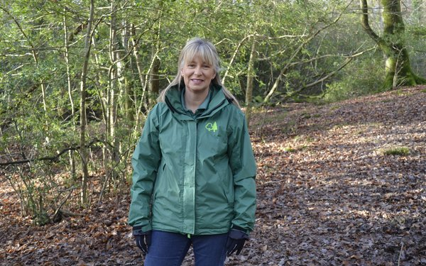Jane, a volunteer ranger stand in a autumnal woodland