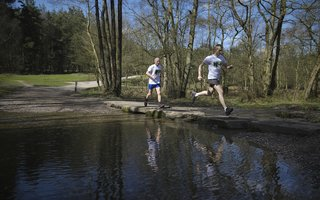 Two men running across stepping stones in a river in the woods