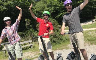 Three guys enjoying Segway in the forest