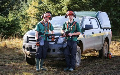 Foresters beside vehicle