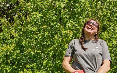 Female forestry volunteer laughing at work