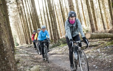 Women cycling in the forest