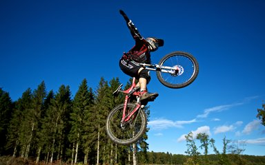 Mountain Biker doing jump and stunts in the forest