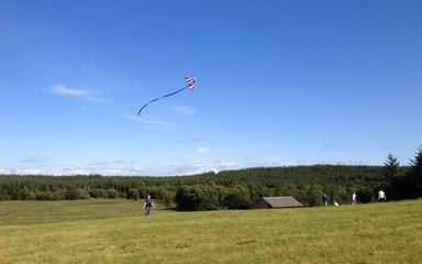 Someone flying a kite in a open field at Gisburn