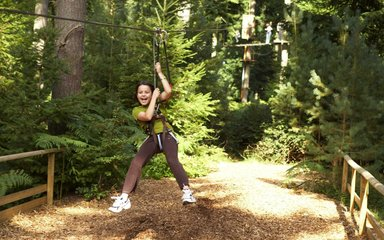 Child flying through the woods on a zip wire