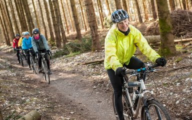 Cyclists riding through the forest on a dirt track