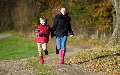Children running on muddy forest path in wellies