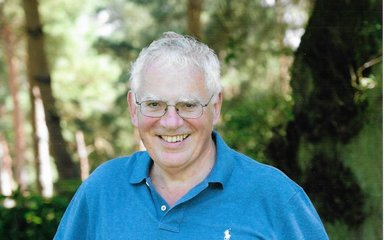 Chris Simpson smiling and standing in front of a wooded area in the sunshine