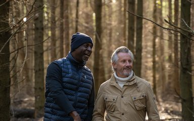 Two men in the forest having a chat and smiling