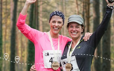 Two women smiling with race medals