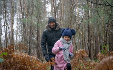 Farther chasing daughter through shrubs in wintery forest