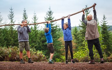 Family lifting branch and playing in front of forest landscape