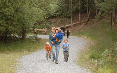 Family walking on gravel path through forest