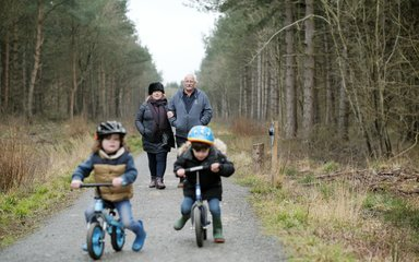 Family walking with boys on balance bikes