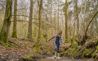 Girl walking through muddy puddle in the forest