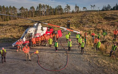 Staff standing by helicopter in forest clearing